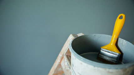 A close shot of a paint can sitting on a ladder