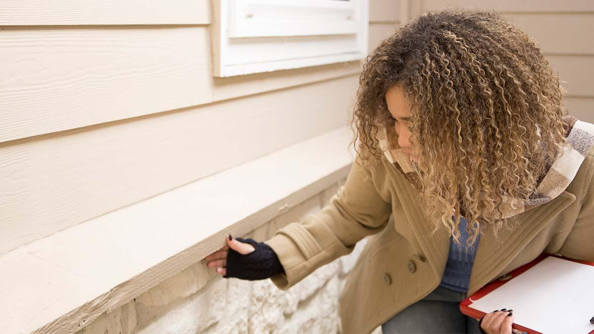 A woman holds a clipboard and inspects the exterior of a house.