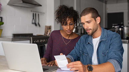 couple looking at computer and papers