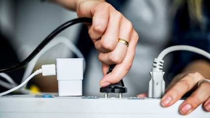 A tight shot of a person plugging a cord into a power strip