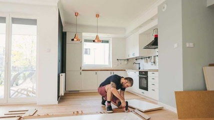 A man working on a home improvement project in a kitchen