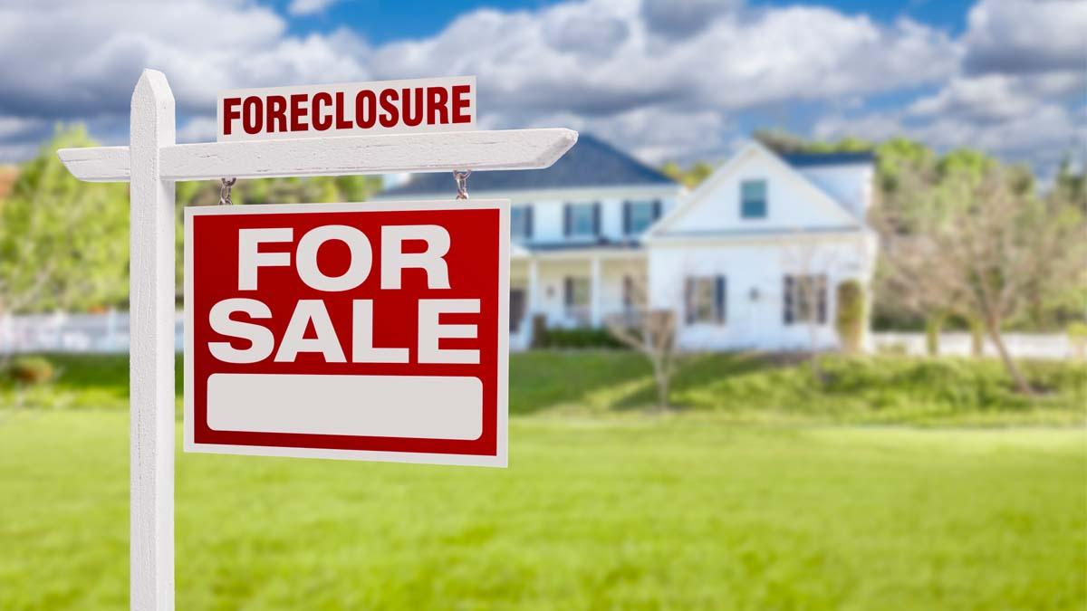 home with a foreclosure for sale sign in front of it