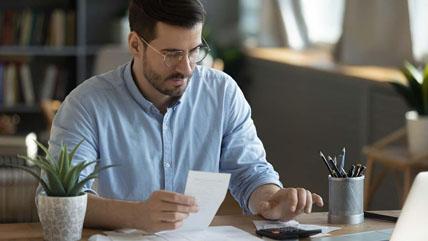 man calculating at his desk