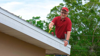 A man in a red shirt inspects the roof of a house