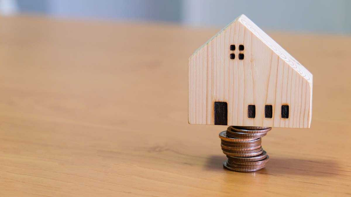 Wooden house on top of coins to represent refinancing a home