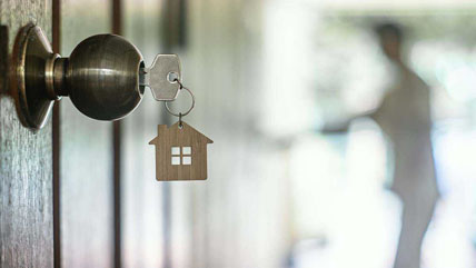 Key in door with house shaped keychain