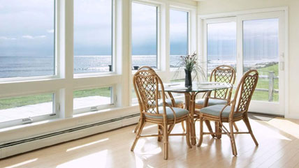 A dining room in a beach house with large windows