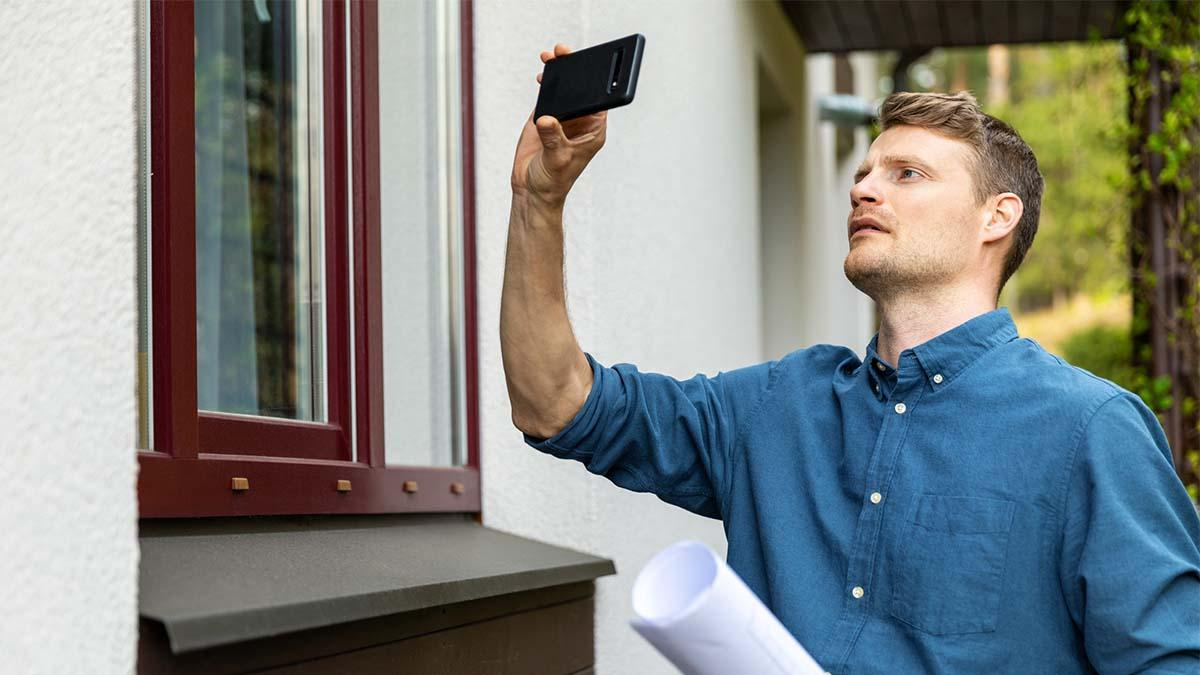 Man inspecting home and taking photos