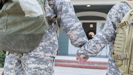 A military couple holds hands