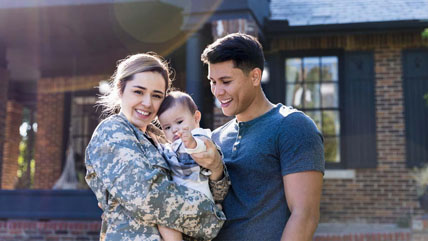A young military family stand in front of their home, smiling.