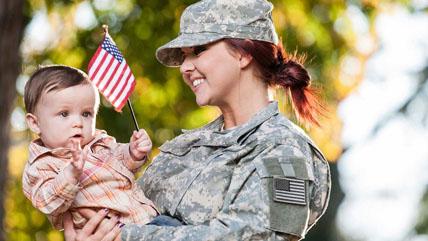 veteran mom holding her baby waving an American flag