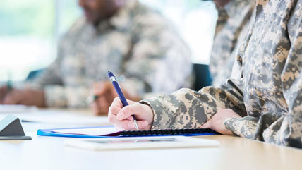 A close up of a veteran's hand filling out paperwork.