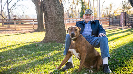 A senior veteran sits outside with his dog