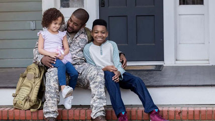 A veteran sits on the steps of his home with his two young children
